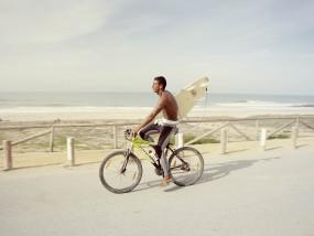 Fietser met surfboard op dijk